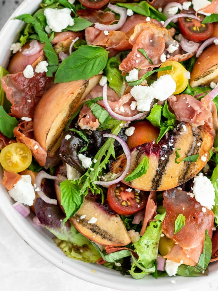 Brightly colored salad with grilled peaches, crispy prosciutto, creamy goat cheese, shallot, basil and greens.