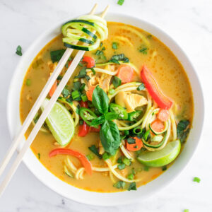 Paleo and Keto Thai Curry Chicken Zoodle Soup with basil, Thai chilis, bell pepper, lime, carrots, and chicken thighs.